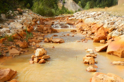 AMD contamination turns rocks orange as well as adds metals and sediments to the creek.
